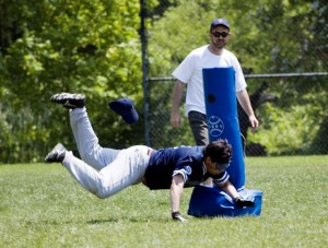 Joe Quintanilla diving into a base against Long Island in 2005 with coach Jason Lenicheck looking on