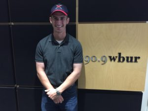 Christian Thaxton stands in front of the WBUR sign